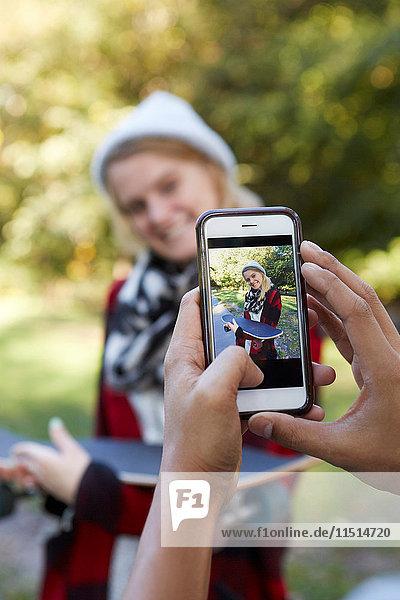 Männliche Hände fotografieren Freundin im Park auf Smartphone