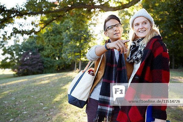Junge Skateboardfahrerin und ihr Freund zeigen im Park