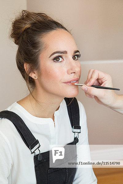 Hand of Make-up Artist beim Auftragen von Lipgloss auf weibliche Mode- und Lifestyle-Bloggerin