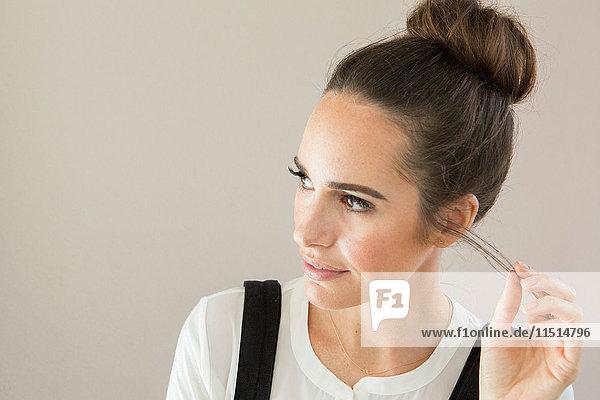 Porträt einer schönen weiblichen Mode- und Lifestyle-Bloggerin  die mit den Haaren spielt