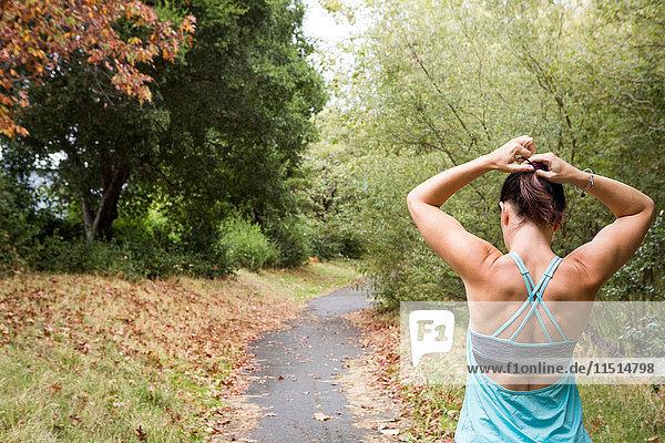 Rear view of female runner tying hair in park