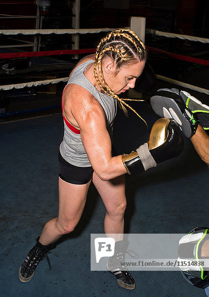 Female boxer punching trainer's boxing mitt in boxing ring
