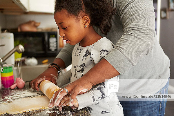Father and daughter baking cookies together  mid section