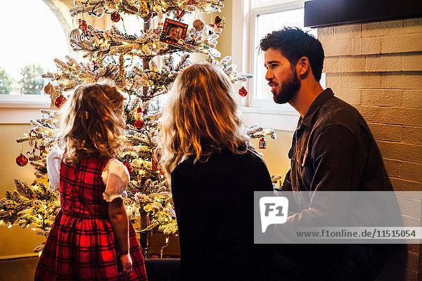 Rückansicht eines weiblichen Kleinkindes mit Eltern  die den Weihnachtsbaum betrachten