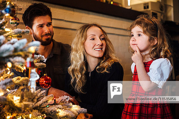 Female toddler with parents gazing at christmas tree