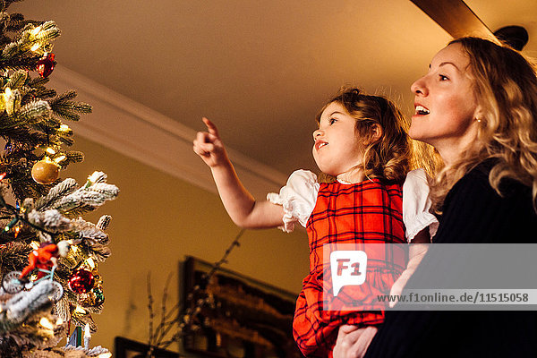 Female toddler with mother pointing at christmas tree bauble
