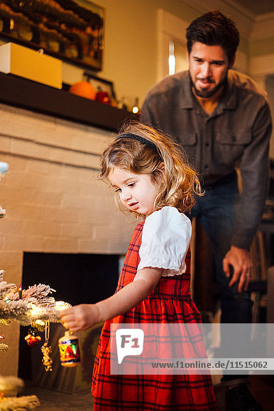 Female toddler with father placing bauble on christmas tree