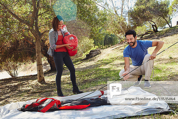 Mid adult couple camping  erecting their tent