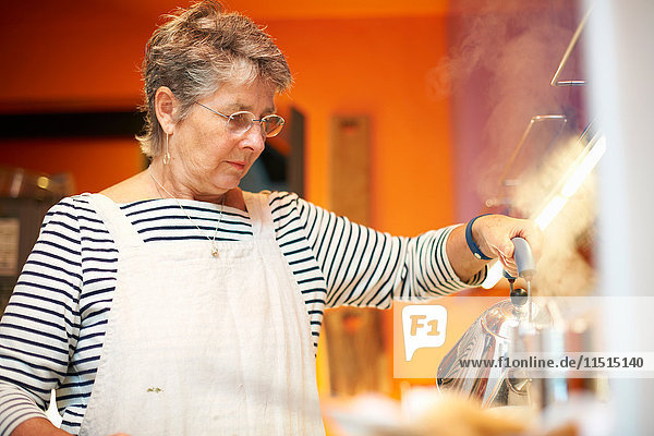 Ältere Frau in der Küche  gießt Wasser aus dem Wasserkocher