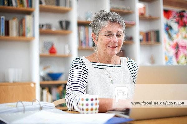 Ältere Frau zu Hause  die einen Laptop benutzt