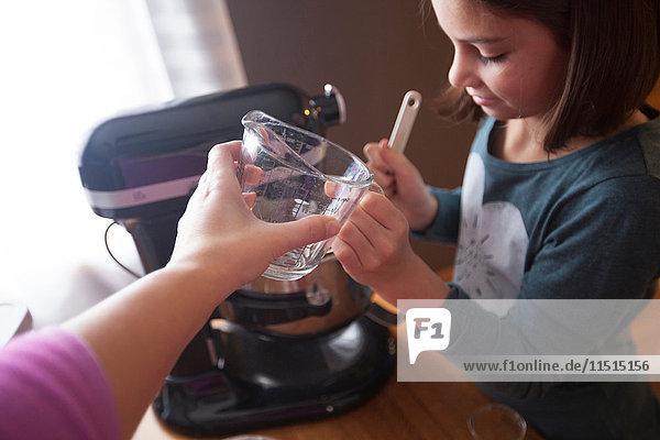 Young girl using food mixer  mother handing daughter measuring jug