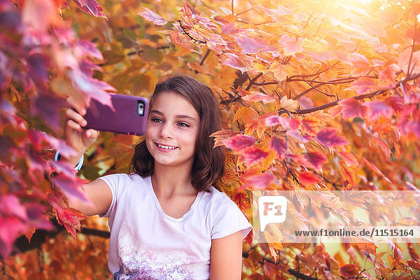 Young girl in rural setting  taking selfie with smartphone