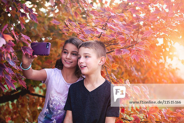 Boy and girl in rural setting  taking selfie with smartphone