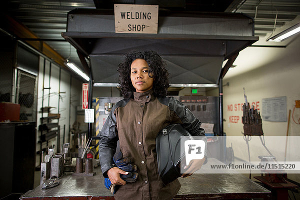 Portrait of young female metalsmith in welding workshop
