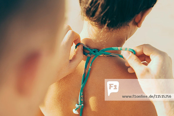 Over shoulder view of man fastening girlfriend's bikini top  Newport Beach  California  USA
