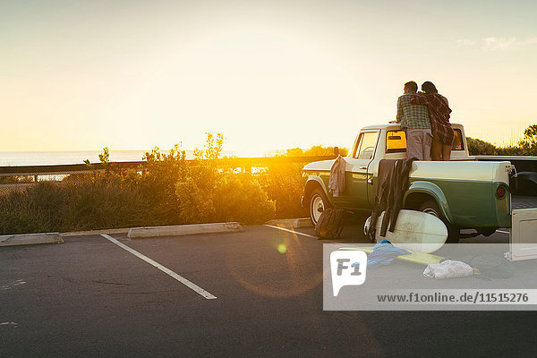 Rückansicht eines Paares hinten im Pick-up  das den Sonnenuntergang in Newport Beach  Kalifornien  USA  beobachtet