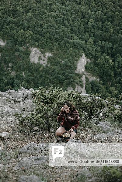 Smiling Caucasian woman crouching on mountain holding pan
