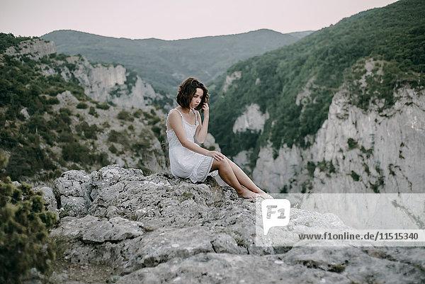 Pensive Caucasian woman sitting on mountain