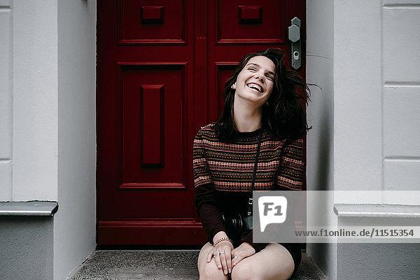 Laughing Caucasian woman sitting in doorway