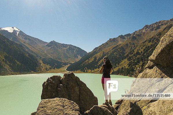 Caucasian woman standing on rocks near mountain lake