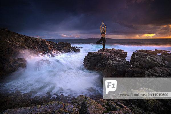 Distant Caucasian woman doing yoga on rocks near ocean
