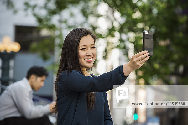 Chinese businesswoman posing for cell phone selfie outdoors