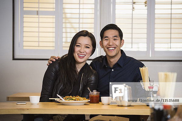 Smiling Chinese couple hugging in restaurant