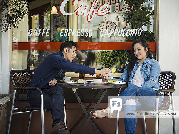 Chinese man tasting food of woman at outdoor cafe