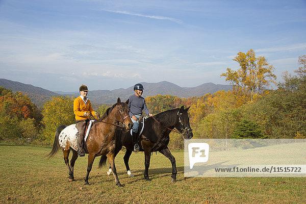 Older Caucasian couple horseback riding in field