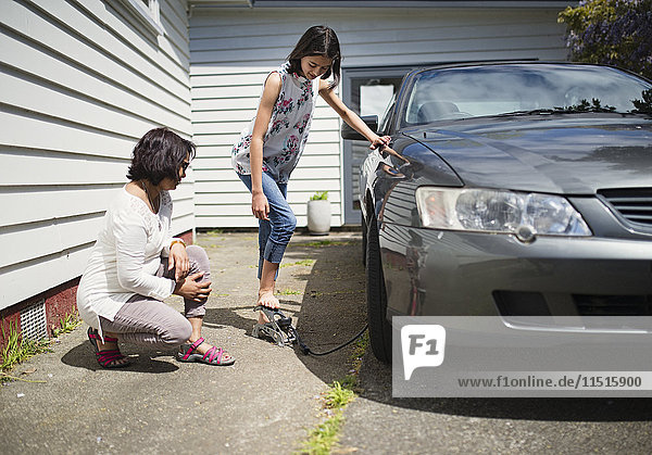 Mother watching daughter inflating car tire
