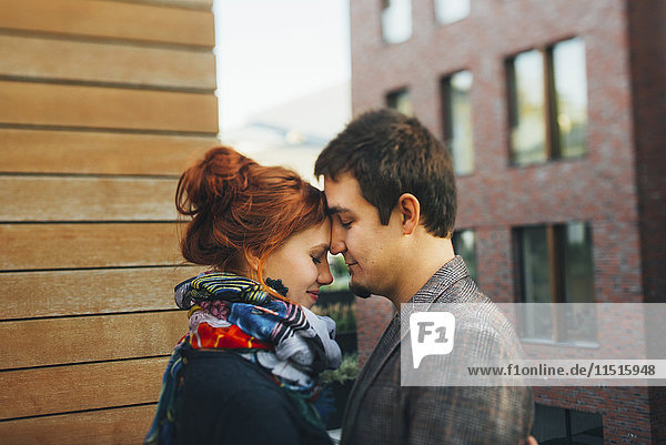Caucasian couple hugging face to face in city