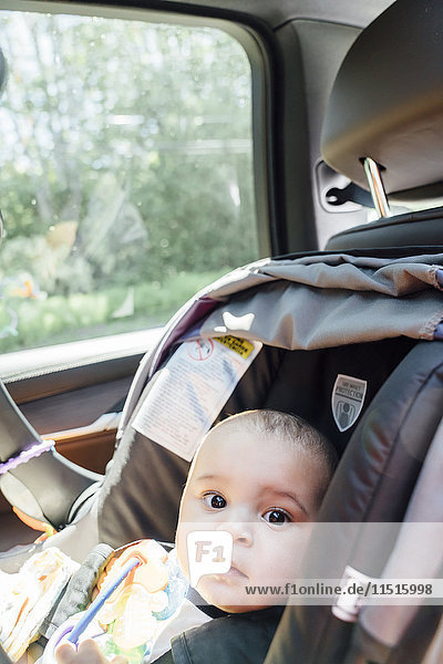 Portrait of curious Mixed Race baby boy in car seat