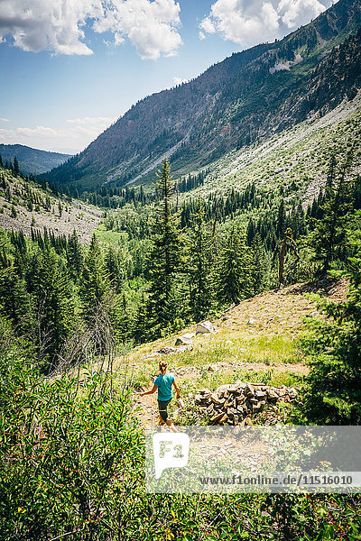 Caucasian woman hiking downhill on path in mountains