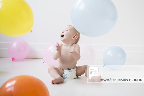 Caucasian baby boy sitting on floor watching balloons