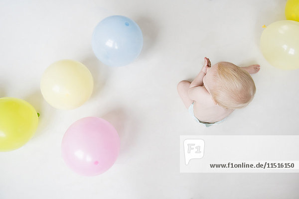Caucasian baby boy sitting on floor with balloons