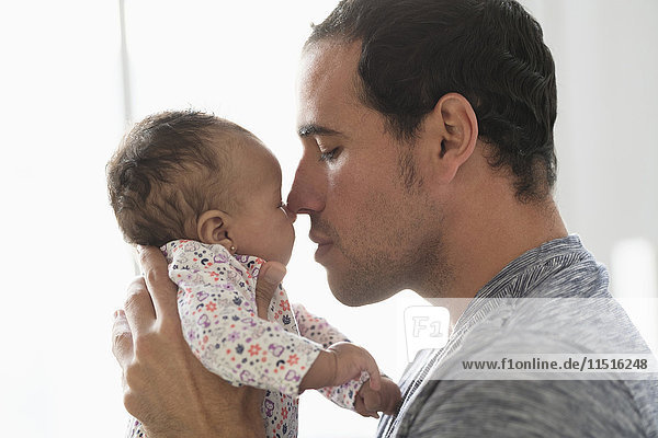 Hispanic father rubbing noses with baby daughter