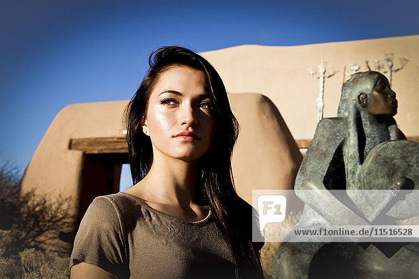 Portrait of Hispanic teenage girl near statue