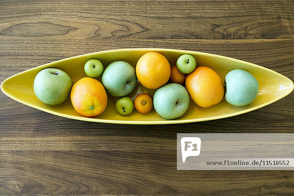 Bowl with fruit on wooden table