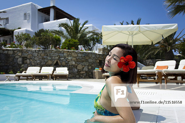Woman with flower in hair relaxing in swimming pool