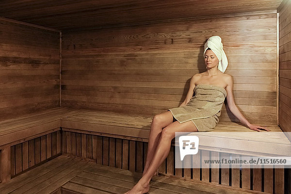 Woman wrapped in towel relaxing in sauna