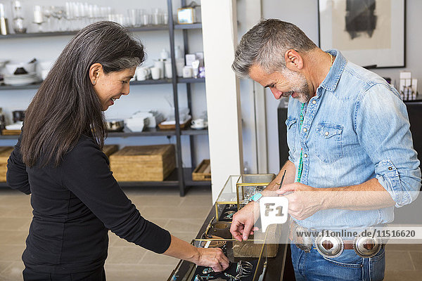 Man and woman examining jewelry in store