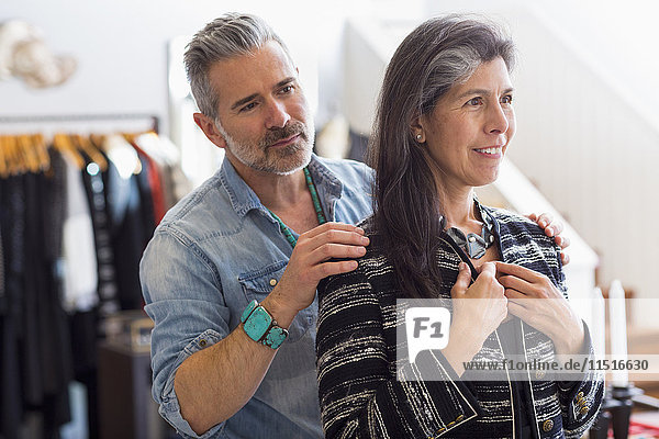 Man helping woman with jacket in store