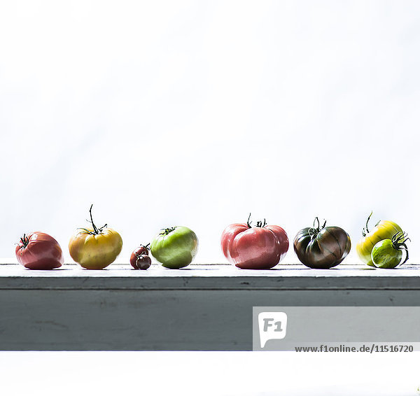 Row of fresh tomatoes on wooden table