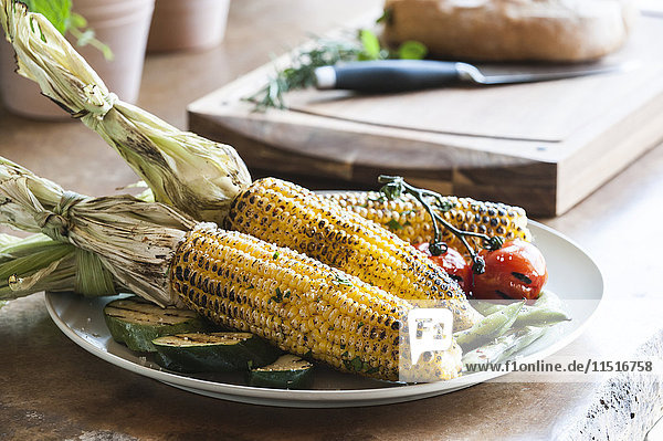 Plate of grilled corn,  tomatoes and zucchini