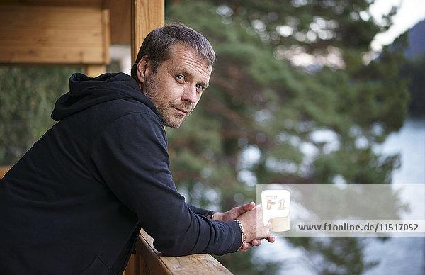 Caucasian man leaning on railing drinking coffee