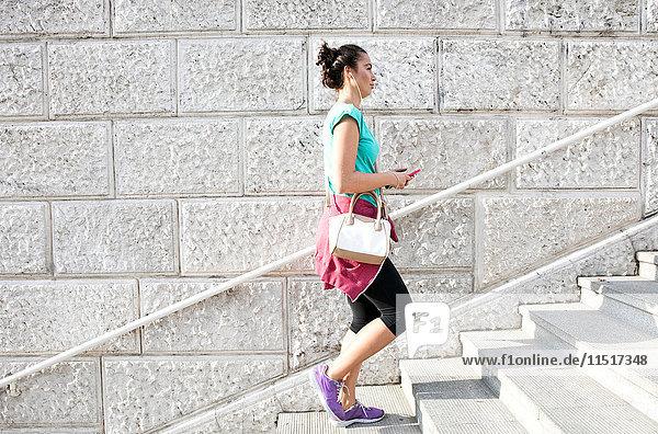 Junge Frau  die Sportkleidung und Kopfhörer trägt und eine Treppe hinaufgeht