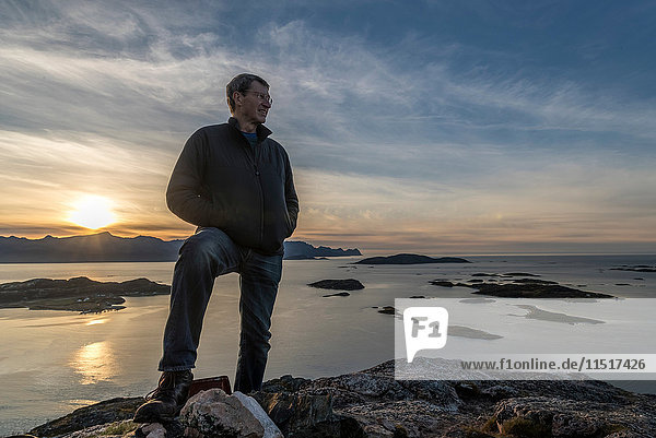 Mann besteigt im Herbst einen Gipfel auf der Insel Kvaloya  Arktis Norwegen