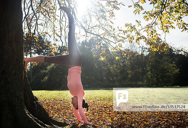 Woman doing yoga in park on autumn day