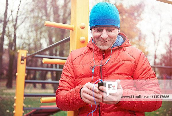 Älterer Mann  im Freien  mit Smartphone  mit Kopfhörern