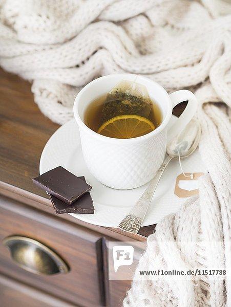 Eine Tasse heisser Tee mit Zitrone  serviert mit dunkler Schokolade